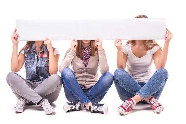 Mädchen sitzen mit gekreuzten beinen und geschlossenen gesichtern weißen tisch.