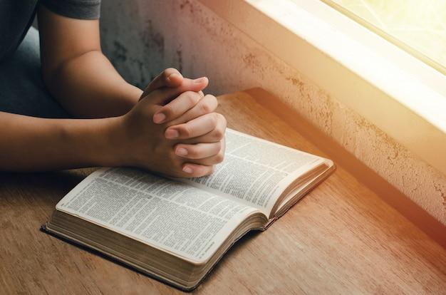 Mädchen sitzen und beten um segen von gott mit der bibel gefalteten händen im biblischen, spirituellen und religiösen gebet kommunizieren, sprechen sie mit gott. liebe und vergebung