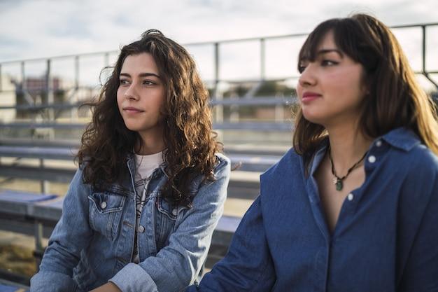 Mädchen sitzen und reden tagsüber hinter einem metallzaun miteinander