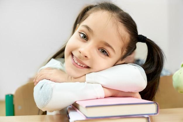 Mädchen sitzt am schreibtisch, stützt sich auf bücher, lächelt.