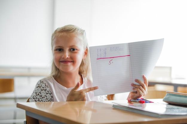 Mädchen sitzt am schultisch mit notebook