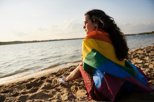 Mädchen sitzt am strand und beobachtet den sonnenuntergang mit regenbogenfahne
