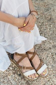 Mädchen sitzt am strand und hält knie. sandalen im griechischen stil