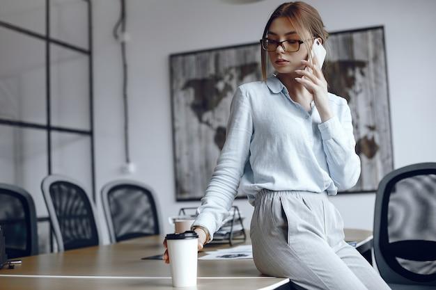 Mädchen sitzt am tisch. frau spricht am telefon. brünette trinkt kaffee