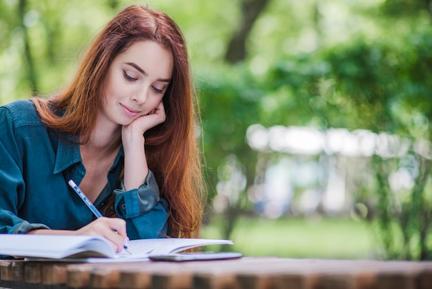 Mädchen sitzt am tisch schriftlich