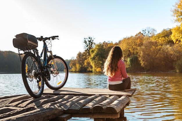 Mädchen sitzt am ufer des flusses. fahrrad auf dem fluss mit einer tasche auf dem kofferraum