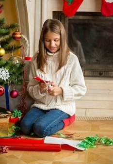 Mädchen sitzt am weihnachtsbaum und schneidet schneeflocken aus dekorativem papier