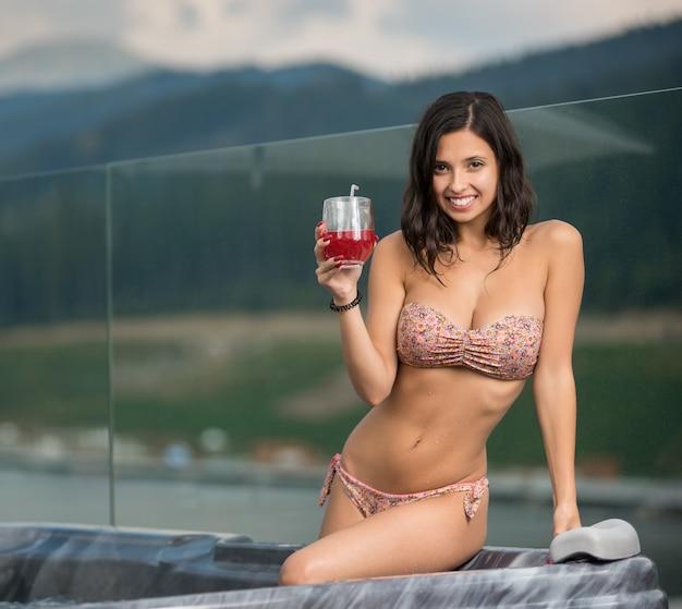 Mädchen sitzt am whirlpool mit cocktail