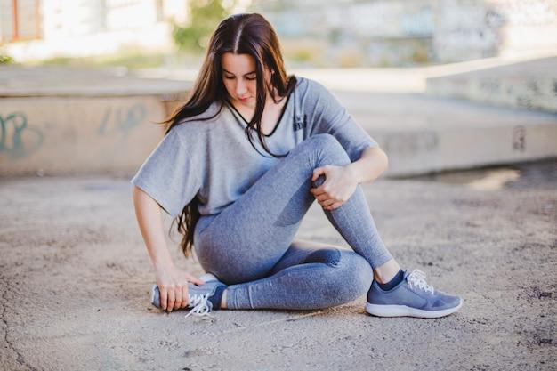 Mädchen sitzt auf betonboden stretching
