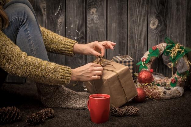 Mädchen sitzt auf dem boden mit einer roten tasse in der hand, umgeben von weihnachtsschmuck