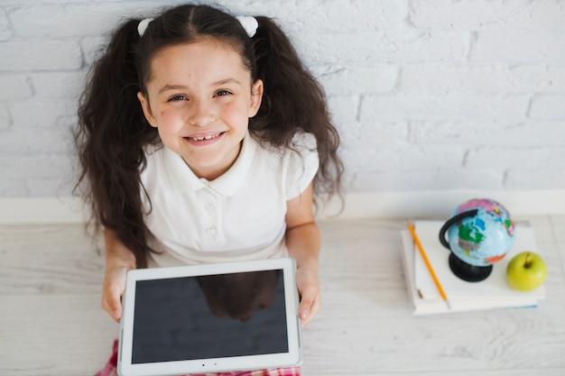 Mädchen sitzt auf dem boden mit tablette