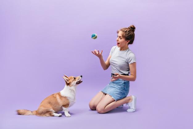 Mädchen sitzt auf dem boden und spielt mit hund. glückliche junge frau in den weißen turnschuhen, die mit ball und corgi auf lila hintergrund aufwerfen.