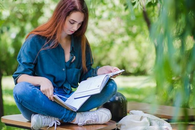 Mädchen sitzt auf dem tisch im park lesen