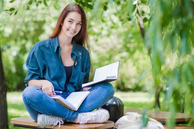 Mädchen sitzt auf dem tisch mit lehrbuch lächelnd