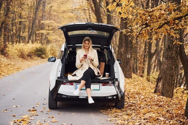 Mädchen sitzt auf der rückseite des autos. modernes brandneues auto im wald.