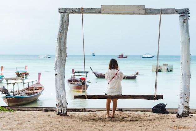 Mädchen sitzt auf der schaukel am tropischen strand