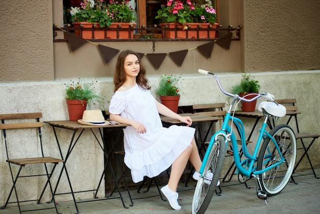 Mädchen sitzt auf der terrasse eines straßencafés neben einem stehenden blauen retro-fahrrad