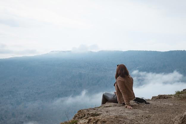 Mädchen sitzt auf einem felsen, blick von hinten, herbstlandschaft, berge und nebel