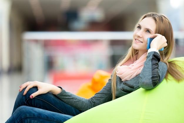 Mädchen sitzt auf einem sofa auf ihrem handy spricht