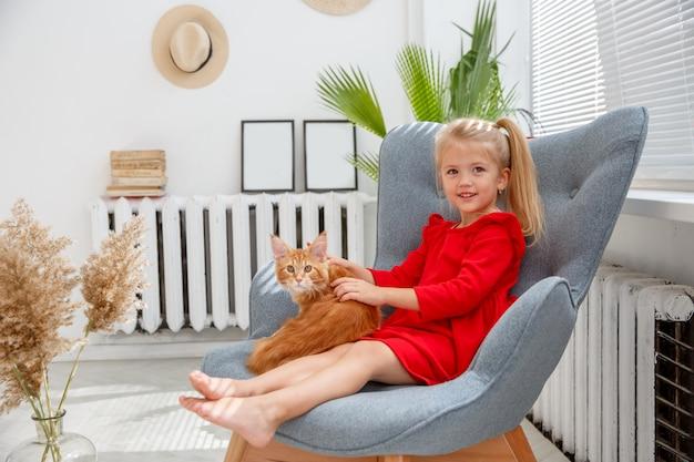 Mädchen sitzt auf einem stuhl mit einer katze