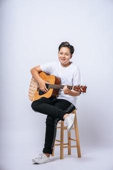 Mädchen sitzt auf einem stuhl und spielt gitarre.