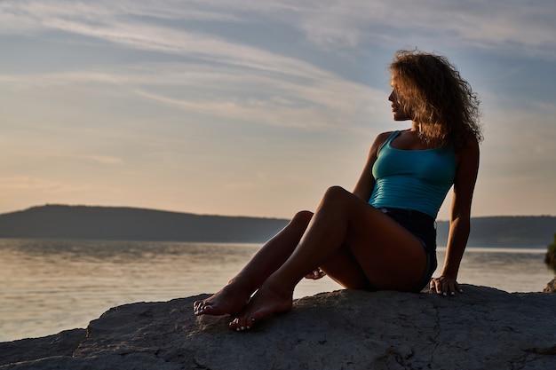 Mädchen sitzt auf steinen und bewundert die landschaft