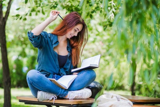 Mädchen sitzt auf tisch im park lächelnd