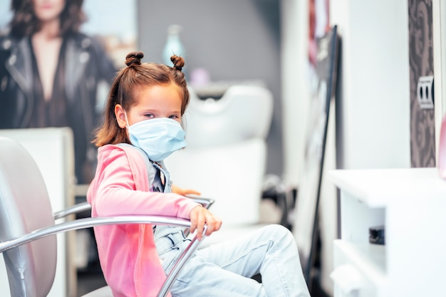 Mädchen sitzt im friseurstuhl mit den zöpfen fertig. wiedereröffnung mit sicherheitsmaßnahmen für friseure in der covid-19-pandemie