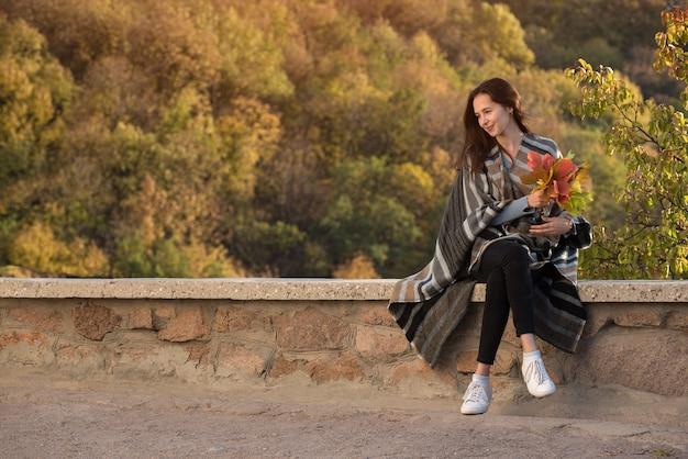 Mädchen sitzt im hintergrund der natur mit einem blumenstrauß von herbstblättern