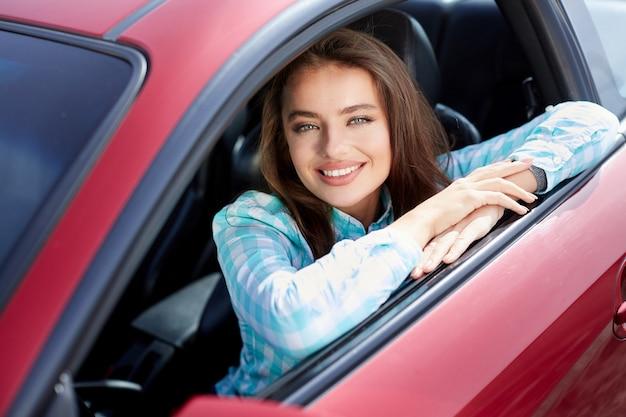 Mädchen sitzt im roten auto, glücklicher fahrer. frau, die kamera betrachtet und lächelt. kopf und schultern des glücklichen besitzers eines neuen autos, der sich auf das auto stützt und nach draußen schaut