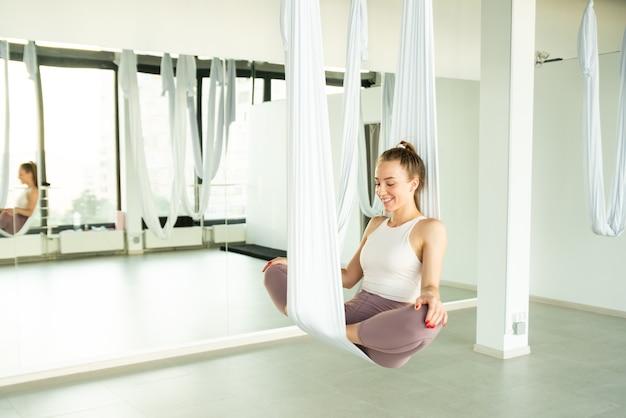 Mädchen sitzt in einer lotusposition in einer hängematte für aerial yoga und macht mudras-entspannung in yoga-kursen