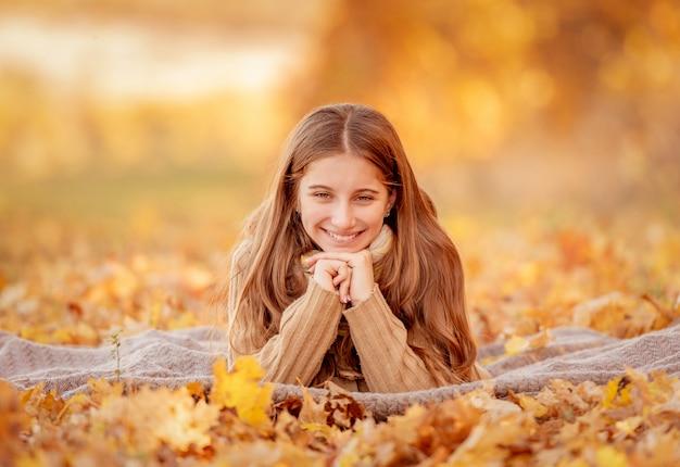 Mädchen sitzt in gelben blättern