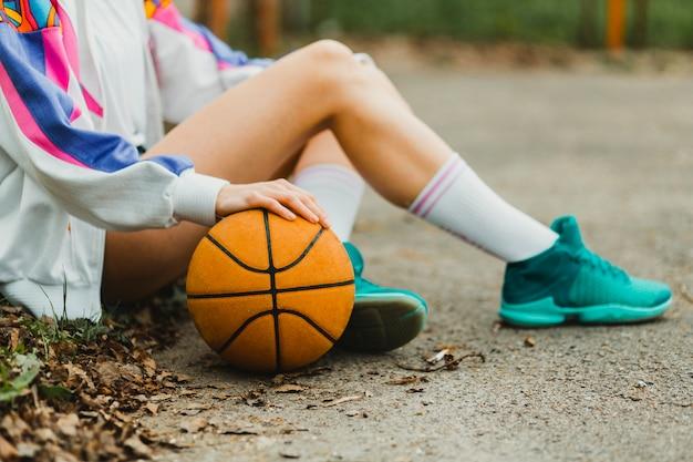 Mädchen sitzt mit basketball