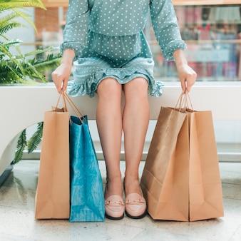 Mädchen sitzt mit einkaufstüten