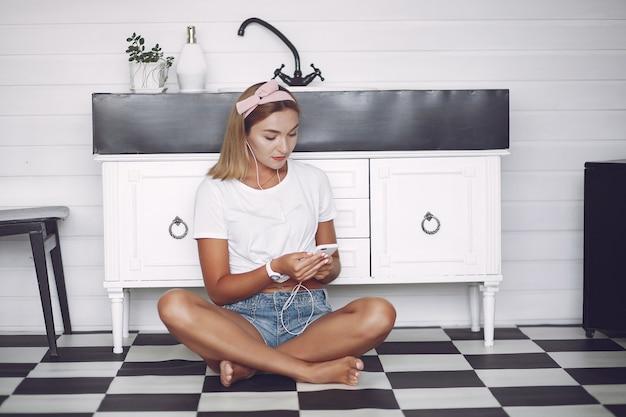 Mädchen sitzt zu hause und benutzt das telefon