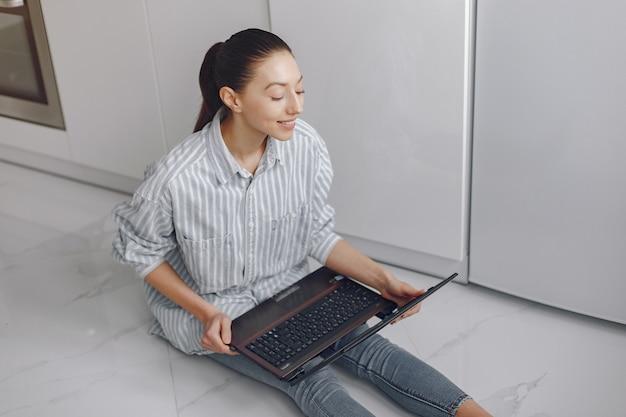 Mädchen sitzt zu hause und benutzt den laptop