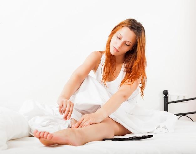Mädchen sorgt für zehennägel mit schere im bett zu hause