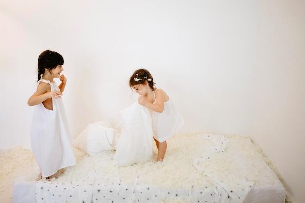 Mädchen spielen auf der matratze
