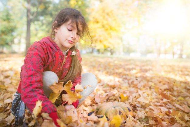 Mädchen spielen mit gelben ahornblättern beim gehen im sonnigen herbstpark