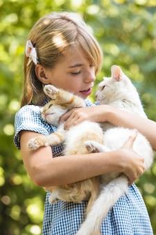 Mädchen spielen mit kätzchen im freien im park