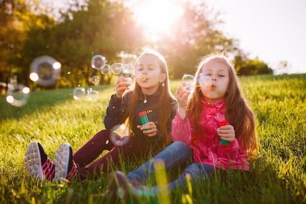 Mädchen spielen mit seifenblasen.