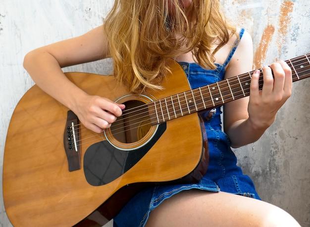 Mädchen spielt akustikgitarre.
