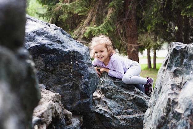 Mädchen spielt auf felsen, klettern, kindheit und freude, spielt mit anderen kindern, entwicklung