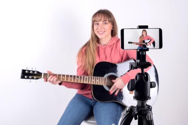 Mädchen spielt die gitarre, um sie in sozialen netzwerken zu teilen