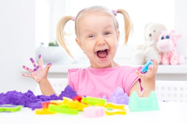 Mädchen spielt kinetischen sand in quarantäne. blondes mädchen lächelt und spielt mit lila sand auf einem weißen tisch.