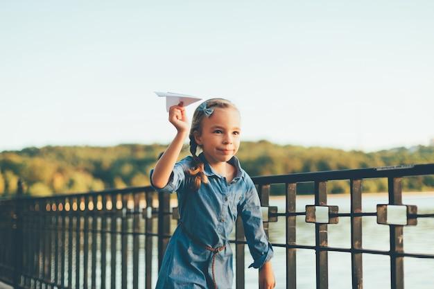 Mädchen spielt, läuft mit spielzeugpapierflugzeug