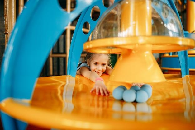 Mädchen spielt mit bällen auf luftmaschine, spielzentrum