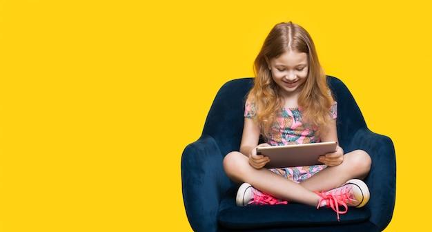 Mädchen spielt mit einer tablette, die in einem sessel sitzt