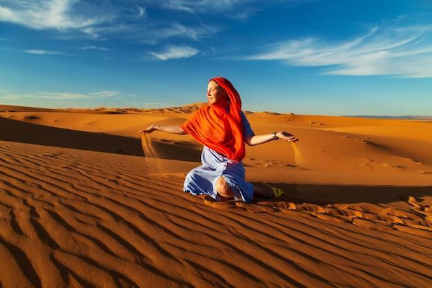 Mädchen spielt mit sand in der sahara. erg chebbi, merzouga, marokko.