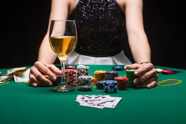 Mädchen spielt poker in einem casino mit chips, dollar und wein